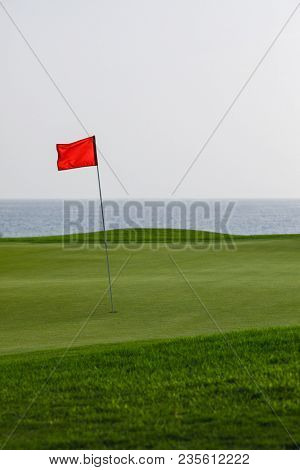 golf course with green grass and red pin flag, sea background