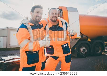 Garbage removal workers giving a thumbs-up in front of disposal truck