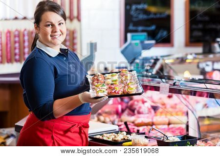 Sales woman in butcher shop offering finger food and party service