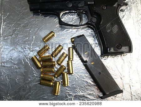 Gun And Brass Bullets On Silver Shiny Surface