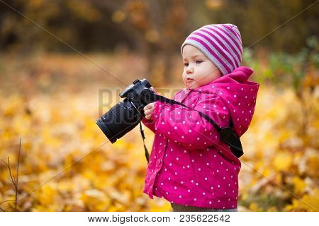 Little Kid Is Playing With Camera And Taking Photo Of Autumn Nature As Master. Baby Is In Autumn Par