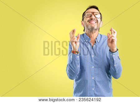 Handsome middle age man with crossed fingers asking for good luck