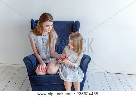 Two Happy Kids Sitting On Modern Cozy Blue Chair Relaxing In White Living Room At Home. Adorable Pre