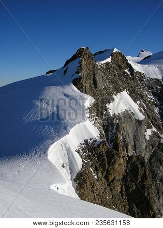 The Peak Of Corno Nero In Wallis Alps Half Covered By Snow.