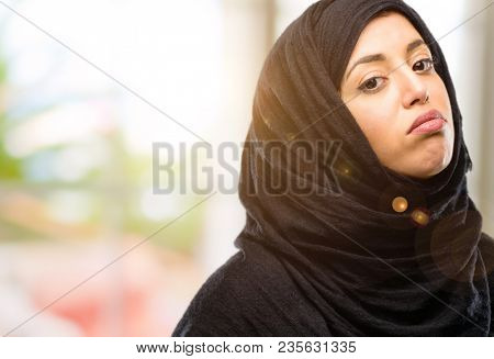 Young arab woman wearing hijab with sleepy expression, being overworked and tired
