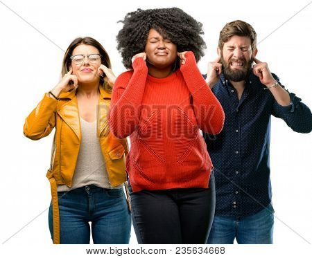 Group of three young men and women covering ears ignoring annoying loud noise, plugs ears to avoid hearing sound. Noisy music is a problem.