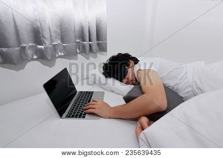 Tired Overworked Asian Man With Laptop Sleeping On The Bed.