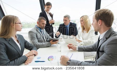 Business person group in formalwear discuss documents at meeting in modern office