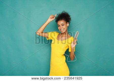 Lovely Melody. Woman Listen To Music In Earphones, Standing On Blue Studio Background, Copy Space