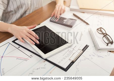 Closeup Of Woman Hands Counting On Calculator And Using Digital Tablet With Blank Screen For Adverti