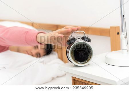 The Young Man Was Awakened By The Morning Alarm Clock While On The Bed.shallow Depth Of Field. Coffe
