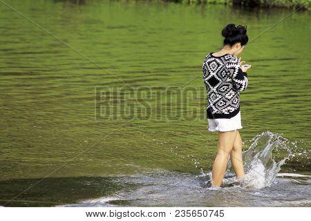 Girl Kicks Water And Takes A Photo.