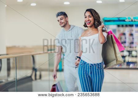 Happy Young Couple With Shopping Bags Walking In Mall - Sale, Consumerism And People Concept