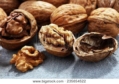Walnut Kernels And Whole Walnuts On Rustic Old Table