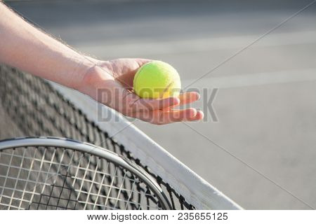 Sportsman Is Playing Tennis On Court Outdoor. Hand Gives Yellow Tennis Ball Over Net To Other Player