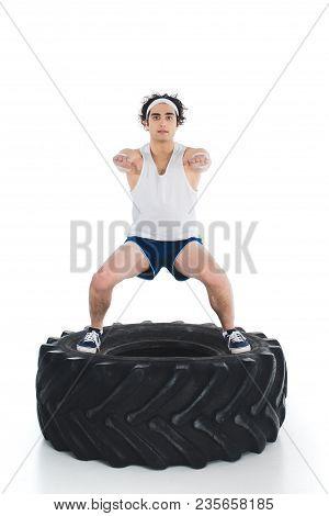 Skinny Sportsman Exercising On Tire Of Wheel Isolated On White