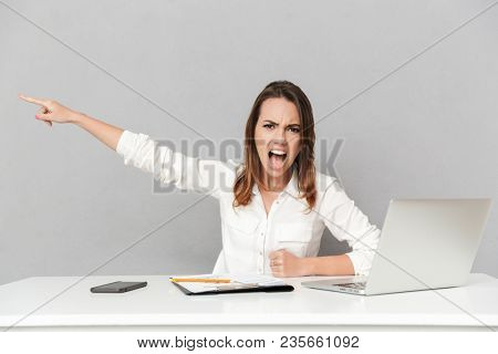 Portrait of an angry young business woman sitting at the office desk and yelling isolated over white background