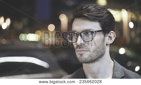 Three Quarters Of A Bearded Man Wearing Glasses On The Street At Night. A Hipster In A Night Time In
