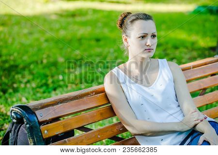 Beautiful Russian Girl Sitting On Bench In Park