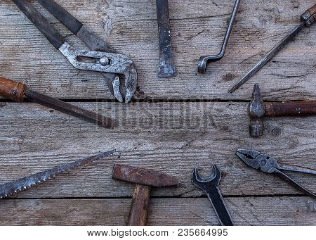 Old, Rusty Tools Lying On A Black Wooden Table. Hammer, Chisel, Hacksaw, Metal Wrench. Copy Space