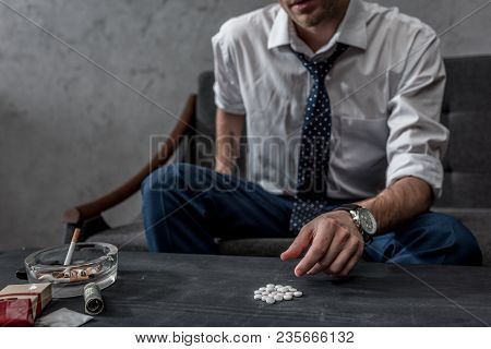 Addicted Junkie In White Shirt And Necktie Taking Mdma Pill From Table