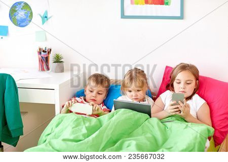 childhood, technology and family concept - little kids with tablet pc computer and smartphones in bed at home