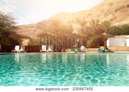 Summer, Travel, Vacation And Holiday Concept. Lounge Chairs Near Swimming Pool Against Judean Desert