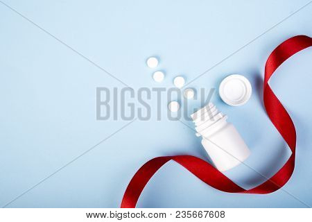 A White Plastic Bottle For Pills And Few Of Them On Blue Background. Copy Space. Ribbon Near The Pil