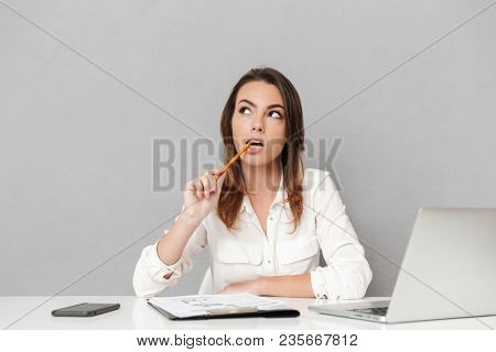 Portrait of a thoughtful young business woman sitting at the office desk isolated over white background