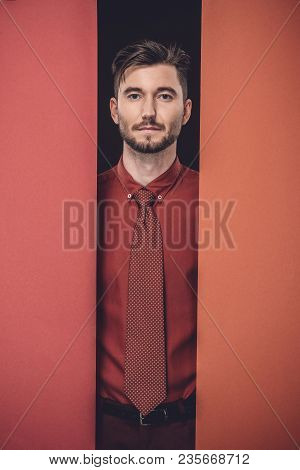 Young Businessman In Red Shirt By Red Paper Walls Isolated On Black