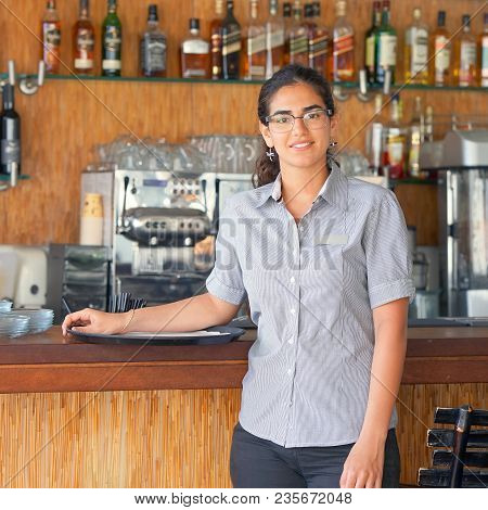 The Waitress Is Standing Near The Restaurant Bar Of The Hotel. A Waitress With A Tray Is Waiting For