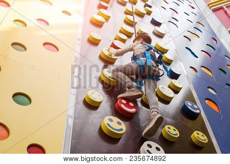 The Stronger You Climb, The Higher Your Pedestal! Small Child Boy As An Alpinist Climbing The Wall I