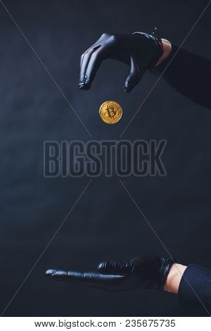 Bitcoin. A Hand Drops A Gold Coin. Hands In Black Gloves. The Concept Of The Fall Of The Crypto Curr