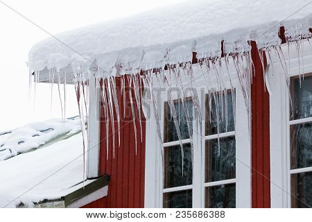 Long Sharp Icicles Hanging Over Windows At Winter