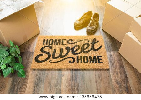 Home Sweet Home Welcome Mat, Moving Boxes, Shoes and Plant on Hard Wood Floors.