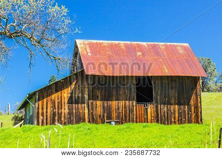 Old Wooden Weathered Barn With Rusty Tin Roof