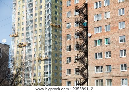 Exterior Work On Unfinished Apartment Block. Builders On Gondolas Perform Finishing Work On A Multi-