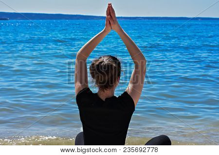 Beautiful Young Woman Is Sitting On A Sandy Beach In Meditation Pose, Doing Yoga.