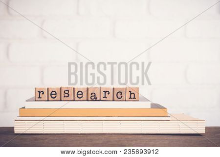 The Word Research, Alphabet On Wooden Cubes On Top Of Books. Background Copy Space, Minimal. Concept