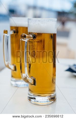 Two Pint Glasses Of Cold Beer Against Sumer Background