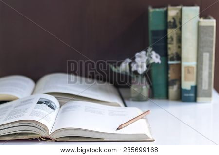 Open Hardback And Textbook Stacked On The Table  Background. The Concept Of Intelligence Comes From