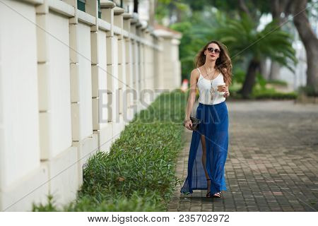 Beautiful Young Woman In Long Silk Skirt Walking In The Park