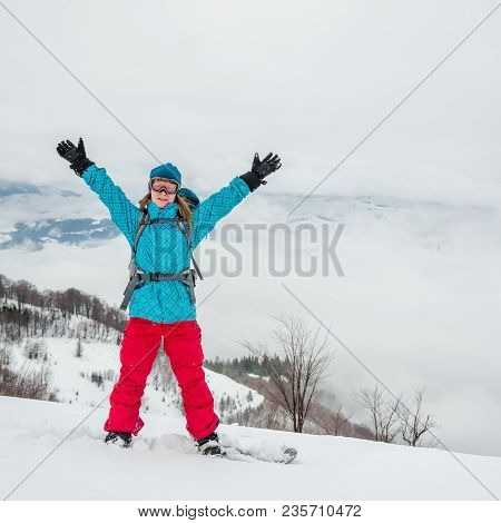 Pretty Young Woman On The Snowboard Standing In The Mountains