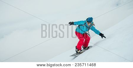 Pretty Young Woman On The Snowboard Riding In The Mountains
