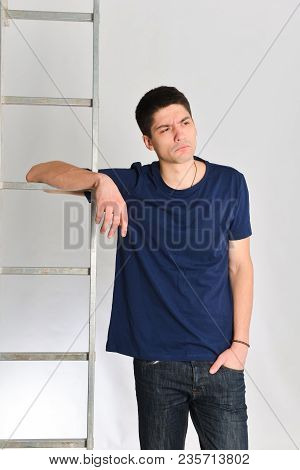 Young Man Posing Next To The Ladder. Repair, Design, Constructor