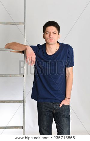 Bewildered Young Man Posing Next To The Ladder. Repair, Design, Constructor