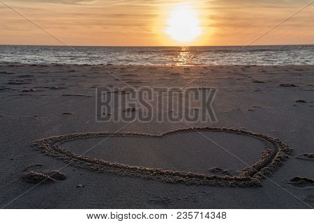 Beautiful Sunset At The Beach With Wooden Piles And Hearts Drawings In The Sand Petten, Holland, Nor