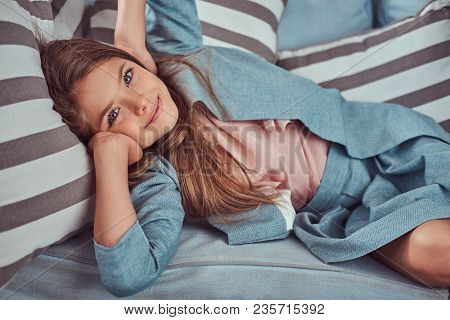 Portrait Of A Cute Little Girl With Long Brown Hair, Piercing Glance And Charming Smile, Looking At