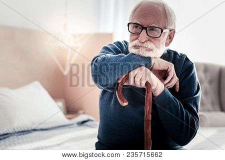Baby Boomer. Serious Thoughtful Age Man Holding A Walking Stick And Leaning On It While Thinking Abo