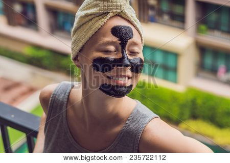 Beautiful Young Woman Relaxing With Face Mask At Beauty Spa. Happy Joyful Woman Applying Black Mask